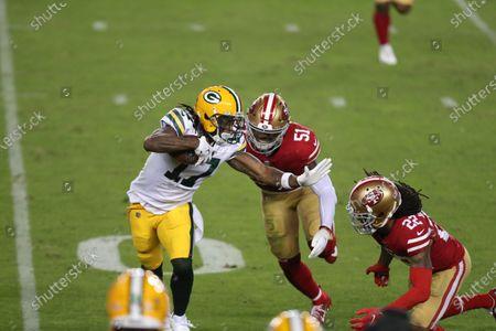 Green Bay Packers wide receiver Davante Adams (17) runs against San Francisco 49ers linebacker Azeez Al-Shaair (51) and cornerback Jason Verrett (22) during the first half of an NFL football game in Santa Clara, Calif