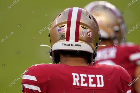 San Francisco 49ers tight end Jordan Reed wears a logo for Salute to Service, the words It Takes All of Us and a 74 for former player Fred Dean before an NFL football game against the Green Bay Packers in Santa Clara, Calif