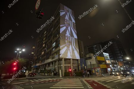 Stock Image of Model wearing a creation from the Alexandre Herchcovitch collection is projected on the facade of a residential building during Fashion Week in Sao Paulo, Brazil