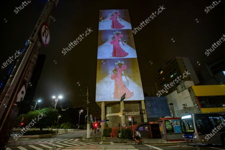 Model wearing a creation from the Alexandre Herchcovitch collection is projected on the facade of a residential building during Fashion Week in Sao Paulo, Brazil