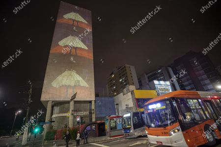 Stock Photo of Model wearing a creation from the Alexandre Herchcovitch collection is projected on the facade of a residential building during Fashion Week in Sao Paulo, Brazil