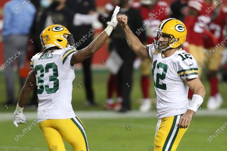 Green Bay Packers quarterback Aaron Rodgers (12) is congratulated by running back Aaron Jones (33) after throwing a touchdown pass to Marcedes Lewis during the first half of an NFL football game against the San Francisco 49ers in Santa Clara, Calif