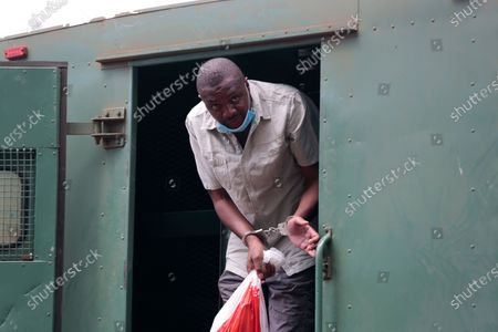 Zimbabwe investigative journalist Hopewell Chin'ono gets out of a prison van at the magistrates courts in handcuffs in Harare, . Chin'ono is one of Zimbabwe's most prominent critics of President Emmerson Mnangagwa's administration, accusing it of corruption and human rights abuses. The government denies the charges