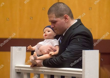 Tony Moreno demonstrates to the jury how he held his son Aaden on the railing of the Arrigoni Bridge in the final moments of Aaden's life, during Moreno's trial Thursday, Feb. 16, 2017, in Middletown, Ct.  Moreno's attorney Norman A. Pattis, left, questions Moreno who took the witness stand on Thursday morning in the fourth day of his murder trial at Middlesex Superior Court. Moreno is charged with murder and risk of injury to a child and is accused of throwing 7-month-old Aaden Moreno to his death from the Arrigoni Bridge on July 5, 2015. Moreno denies intentionally killing his son. (Patrick Raycraft/Hartford Courant via AP, Pool)