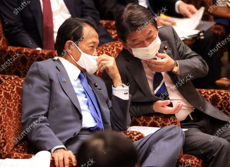 Japanese Finance Minister Taro Aso (L) and Foreign Minister Toshimitsu Motegi (R) share smiles at Upper House's budget committee session at the National Diet in Tokyo on Friday, November 6, 2020.