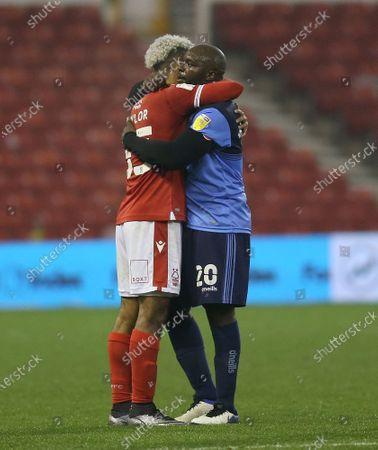 Adebayo Akinfenwa of Wycombe Wanderers hugs Nottingham Forest's Lyle Taylor