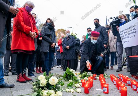 A man places a candle next to Vice President of the German Parliament Claudia Roth (L) after an interconfessional prayer for the victims of the Vienna terror attack at the Austrian embassy in Berlin, Germany, 06 November 2020.