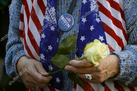 Grace Gardner, a supporter of Vice President Joe Biden, holds a rose as she demonstrates outside the Pennsylvania Convention Center where votes are being counted, in Philadelphia