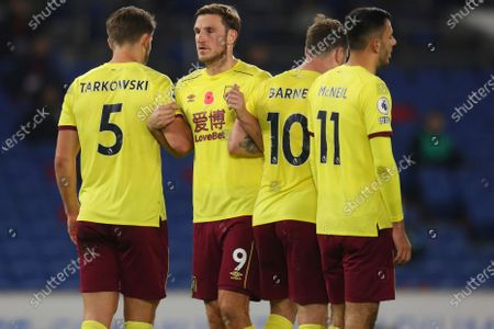 Burnley's Chris Wood, center, wears poppy on his shirt during the English Premier League soccer match between Brighton and Burnley at the Falmer stadium in Brighton, England