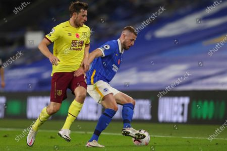 Brighton's Adam Webster, right, is challenged by Burnley's Chris Wood during the English Premier League soccer match between Brighton and Burnley at the Falmer stadium in Brighton, England