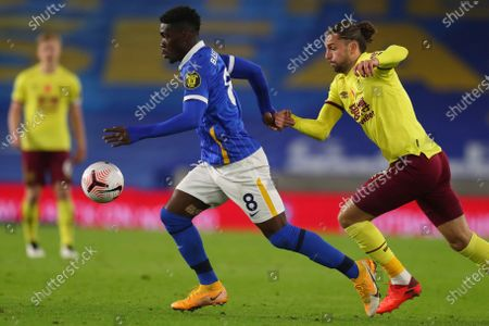 Brighton's Yves Bissouma, left, is challenged by Burnley's Jay Rodriguez during the English Premier League soccer match between Brighton and Burnley at the Falmer stadium in Brighton, England