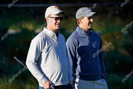 """Peyton Manning, left, and his brother Eli Manning wait to hit from the first tee of the Spyglass Hill Golf Course during the first round of the AT&T Pebble Beach National Pro-Am golf tournament in Pebble Beach, Calif. Both Mannings have become deejays. The former quarterbacks, two-time Super Bowl-winning brothers and close mates with Kenny Chesney, kicked off the """"Poets & Pirates DJ Sessions"""" this week on the singer's SiriusXM channel, No Shoes Radio. In addition to spinning the songs, the Mannings told stories about their personal meanings, as well as about their long-time friendships with Chesney"""