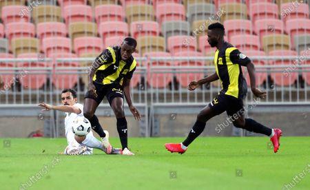 Al-Ittihad's players Abdulaziz Al-Bishi (R) and Saud Abdulhamid (C) in action against Al-Taawoun's Abdullah Al-Jouei (L) during the Saudi Professional League soccer match between Al-Ittihad and Al-Taawoun at King Abdullah Sport City Stadium, 30 kilometers north of Jeddah, Saudi Arabia, 06 November 2020.