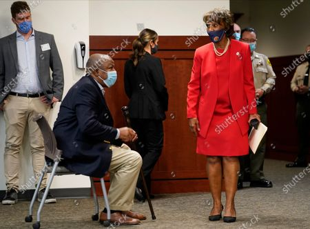 Los Angeles District Attorney Jackie Lacey, right, with her husband David Lacey, sitting left, arrive at a news conference at the Hall of Justice in Los Angeles, . Lacey conceded to former San Francisco District Attorney George Gascon during a news conference
