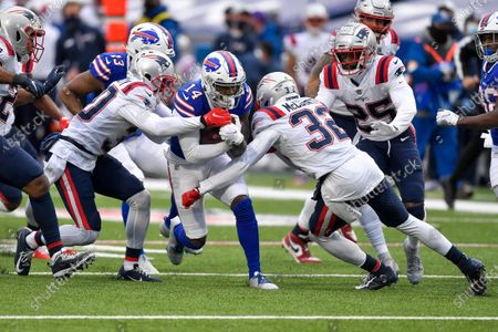 Buffalo Bills wide receiver Stefon Diggs (14) is tackled by New England Patriots cornerback Jason McCourty (30) and defensive back Devin McCourty (32) during the second half of an NFL football game, in Orchard Park, N.Y