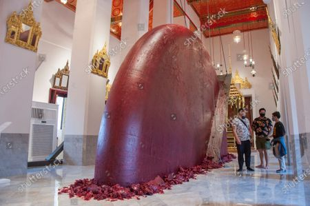 Stock Photo of People are seen talking in front of the sculpture of Sir Anish Kapoor at Wat Pho. Bangkok Art Biennale (BAB) is a biannual art festival set in the capital of Thailand throughout the heart of Bangkok, in galleries, public spaces, temple, and iconic landmarks. Bangkok Art Biennale (BAB) was commenced from 29 October 2020 through to 31 January 2021.