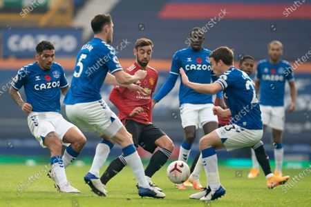 Manchester United's Bruno Fernandes centre left fights for the ball against Everton players including Seamus Coleman second right and Michael Keane second left