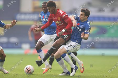 Manchester United's Marcus Rashford, center, is challenged by Everton's Seamus Coleman during the English Premier League soccer match between Everton and Manchester United at the Goodison Park stadium in Liverpool, England