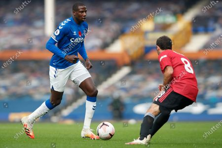 Everton's Abdoulaye Doucoure, left, is challenged by Manchester United's Juan Mata during the English Premier League soccer match between Everton and Manchester United at the Goodison Park stadium in Liverpool, England