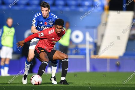 Manchester United's Marcus Rashford, front, fights for the ball with Everton's Seamus Coleman during the English Premier League soccer match between Everton and Manchester United at the Goodison Park stadium in Liverpool, England