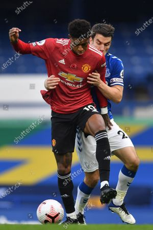 Manchester United's Marcus Rashford, left, fights for the ball with Everton's Seamus Coleman during the English Premier League soccer match between Everton and Manchester United at the Goodison Park stadium in Liverpool, England