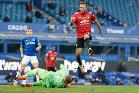 Stock Picture of Manchester United's Juan Mata jumps over Everton's goalkeeper Jordan Pickford during the English Premier League soccer match between Everton and Manchester United at the Goodison Park stadium in Liverpool, England