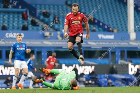 Manchester United's Juan Mata jumps over Everton's goalkeeper Jordan Pickford during the English Premier League soccer match between Everton and Manchester United at the Goodison Park stadium in Liverpool, England