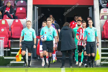 Assistant referee Michael George,referee James Linington,  assistant referee George Byrne lead the players on the pitch before the EFL Sky Bet Championship match between Brentford and Middlesbrough at Brentford Community Stadium, Brentford