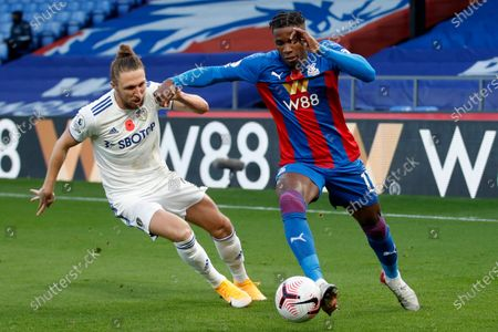 Stock Image of Leeds United's Luke Ayling vies for the ball with Crystal Palace's Wilfried Zaha, right, during the English Premier League soccer match between Crystal Palace and Leeds United at the Selhurst Park stadium in London, England