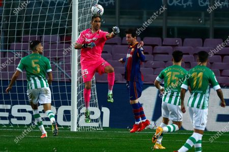 Betis' goalkeeper Claudio Bravo, second left, clears the ball past Barcelona's Lionel Messi, center, during the Spanish La Liga soccer match between FC Barcelona and Betis at the Camp Nou stadium in Barcelona, Spain