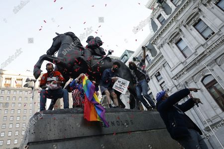 People celebrate upon the statue of Civil War Union Major General John Fulton Reynolds, in Philadelphia, after Democrat Joe Biden defeated President Donald Trump to become 46th president of the United States