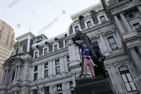 Man dressed as Uncle Same celebrates upon the statue of Civil War Union Major General John Fulton Reynolds, outside City Hall in Philadelphia, after Democrat Joe Biden defeated President Donald Trump to become 46th president of the United States