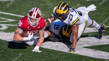 Indiana tight end Peyton Hendershot (86) dives for first-down yardage as he's stopped by Michigan defensive lineman Kwity Paye (19) and linebacker Michael Barrett (23) during the second half of an NCAA college football game, in Bloomington, Ind. Indiana won 38-21