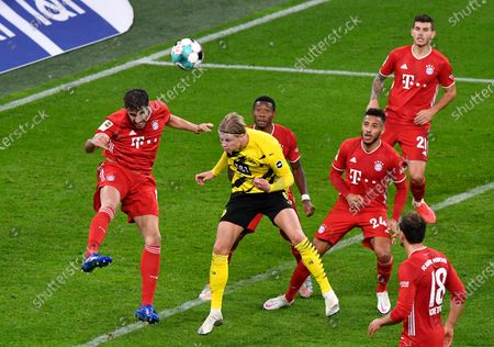 Bayern's Javi Martinez, left, and Dortmund's Erling Haaland challenge for the ball during the German Bundesliga soccer match between Borussia Dortmund and Bayern Munich in Dortmund, Germany