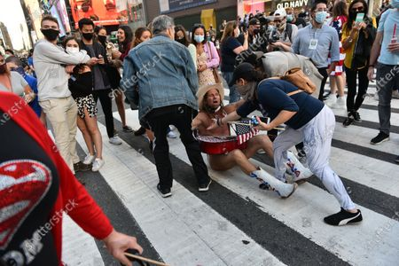 The Naked Cowboy, a known Trump supporter, is knocked to the ground and has his underwear ripped  in Times Square as people celebrate the presidential election results that Joe Biden has defeated incumbent President Donald Trump.