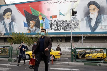 Iranians walk past in front a huge wall painting depicting pictures of Iranian supreme leader ayatollah Ali Khamenei (Top-L), and Iranian late supreme leader Ayatollah Ruhollah Khomeini (Top-R), in a street of Tehran, Iran, 07 November 2020. Iranian government announced earlier that the outcome of the US presidential elecions would make no difference to Iran. However, Iranian president Rouhani on 07 November expressed his hopes that the next US administration returned to the nuclear deal.