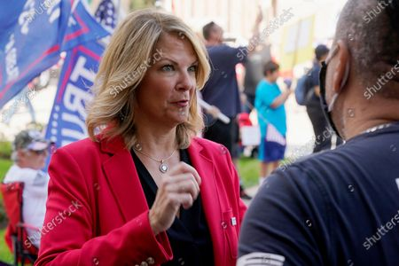 Stock Image of Dr. Kelli Ward, left, Chair of the Arizona Republican Party, talks with a supporter of President Donald Trump as they join the crowd at a rally outside the Arizona state capitol, in Phoenix. Democrat Joe Biden defeated President Donald Trump to become the 46th president of the United States on Saturday, positioning himself to lead a nation gripped by the historic pandemic and a confluence of economic and social turmoil
