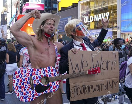 The 'Naked Cowboy,' a Times Square fixture, poses with an Andy Warhol impersonator as people celebrate after major news organizations called the US 2020 presidential election for Joe Biden, defeating  incumbent US President Donald J. Trump, in New York, New York, USA, 07 November 2020.