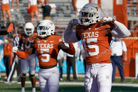 Texas' Chris Brown (15) and D'Shawn Jamison (5) celebrates after a stop against West Virginia on fourth down late during the second half of an NCAA college football game in Austin, Texas