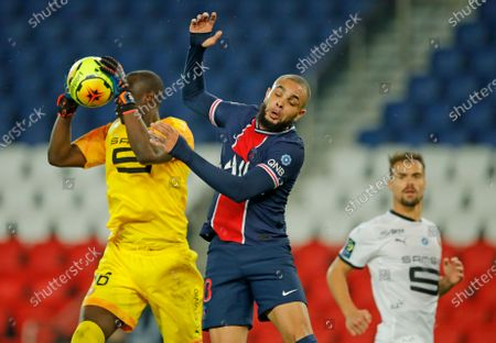 Rennes' goalkeeper Alfred Gomis, left, catches the ball despite the challenge of PSG's Layvin Kurzawa during the French League One soccer match between Paris Saint-Germain and Rennes at the Parc des Princes in Paris, France