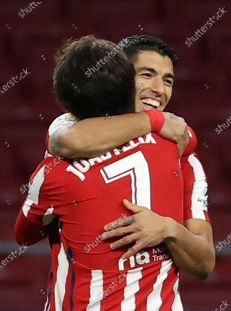 Atletico Madrid's striker Luis Suarez (back) celebrates with teammate Joao Felix (front) after scoring the 3-0 goal during the Spanish LaLiga soccer match between Atletico Madrid and Cadiz CF held at Wanda Metropolitano stadium in Madrid, central Spain, 07 November 2020.