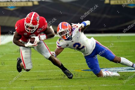 Georgia running back Zamir White, left, is stopped by Florida defensive back Brad Stewart Jr. (2) during the first half of an NCAA college football game, in Jacksonville, Fla