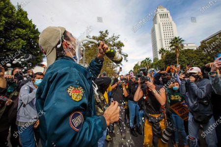 Stock Photo of Evan Sagadencky celebrates Biden/Harris win with champagne in font of City Hall on Saturday, Nov. 7, 2020 in Los Angeles, CA. (Irfan Khan / Los Angeles Times)