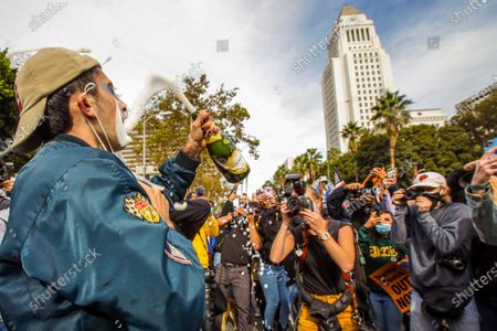 Stock Picture of Evan Sagadencky celebrates Biden/Harris win with champagne in font of City Hall on Saturday, Nov. 7, 2020 in Los Angeles, CA. (Irfan Khan / Los Angeles Times)