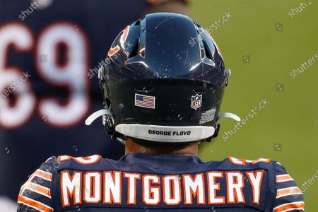 """Chicago Bears running back David Montgomery (32) wears an """"George Floyd"""" sticker on the back of his helmet during the first half of an NFL football game against the New Orleans Saints, in Chicago"""