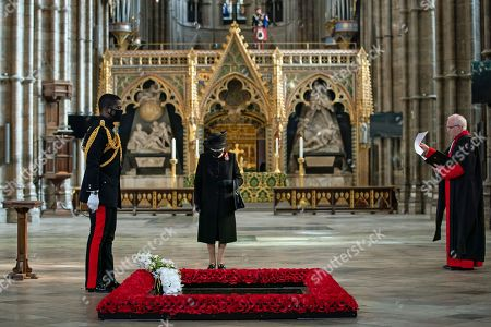 The The Very Reverend John Hall Abbey David Hoyle (right) watches as The Queen's Equerry, Lieutenant Colonel Nana Kofi Twumasi-Ankrah, places a bouquet of flowers at the grave of the Unknown Warrior in front of Queen Elizabeth II during a ceremony in Westminster Abbey, London.