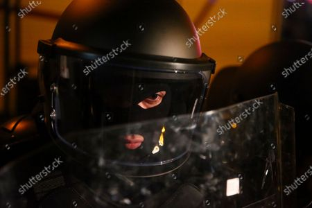 Riot police officer stands in a police line to block supporters for the ex-President Mikhail Saakashvili's United National Movement, protesting the election results in front of the parliament's building in Tbilisi, Georgia, on . Thousands of opposition supporters rallied Sunday in ex-Soviet Georgia to demand a snap vote after the opposition accused the ruling party of rigging tightly contested parliamentary elections