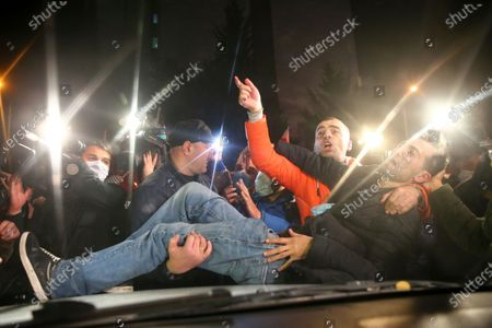 Wounded man is helped during clashes with police and supporters for the ex-President Mikhail Saakashvili's United National Movement, protesting the election results in front of the parliament's building in Tbilisi, Georgia, on . Thousands of opposition supporters rallied Sunday in ex-Soviet Georgia to demand a snap vote after the opposition accused the ruling party of rigging tightly contested parliamentary elections
