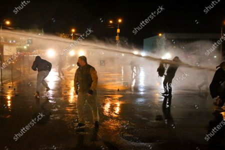 Police use a water cannon toward supporters for the ex-President Mikhail Saakashvili's United National Movement, protesting the election results in front of the parliament's building in Tbilisi, Georgia, on . Thousands of opposition supporters rallied Sunday in ex-Soviet Georgia to demand a snap vote after the opposition accused the ruling party of rigging tightly contested parliamentary elections