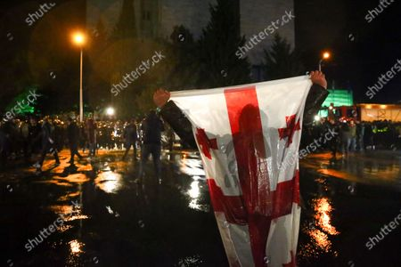 Protester holds a Georgian national flag as other demonstrators clash with riot police during a rally of supporters of the ex-President Mikhail Saakashvili's United National Movement, protesting the election results in Tbilisi, Georgia, on . Thousands of opposition supporters rallied Sunday in ex-Soviet Georgia to demand a snap vote after the opposition accused the ruling party of rigging tightly contested parliamentary elections